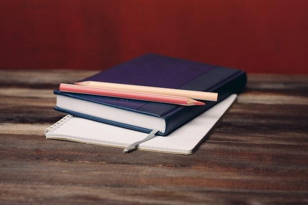 Książka z notatnika ołówki dokumenty biurowe obiekt na drewnianym stole