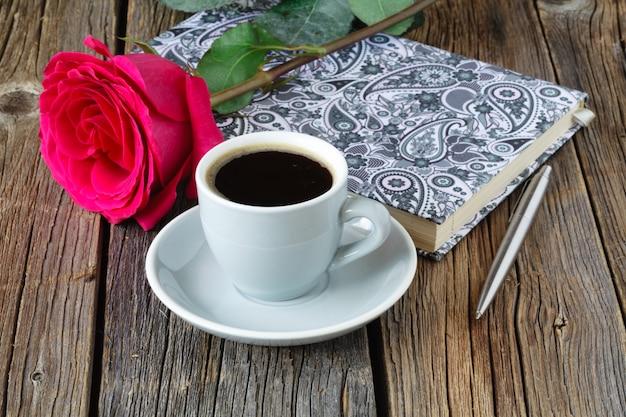 Książka z pięknymi różami i filiżanką kawy na drewnianym stołu zakończeniu up