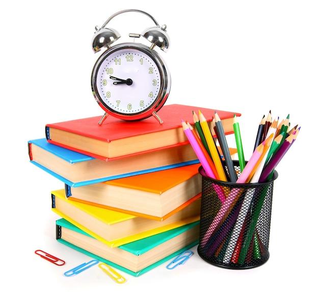 Książki, budzik i narzędzia szkolne na białym tle.
