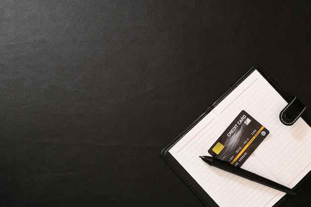 Książki do nagrywania, długopisy, karty kredytowe na biurku. widok z góry