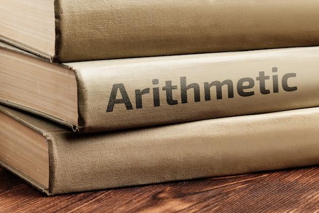 Książki edukacyjne o arytmetyce leżą na drewnianym stole.