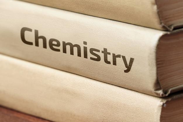 Książki edukacyjne o chemii leżą na drewnianym stole.