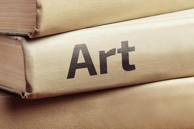 Książki edukacyjne o sztuce leżą na drewnianym stole.