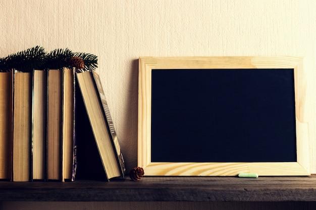 Książki i choinka z szyszek na starej drewnianej półce.