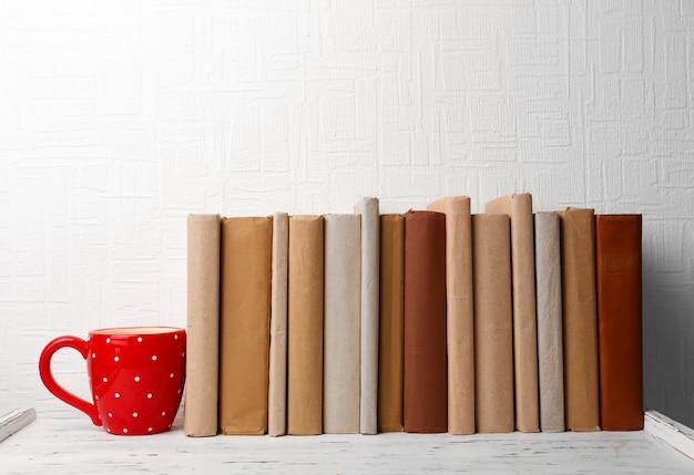 Książki i filiżanka na drewnianej półce na ścianie
