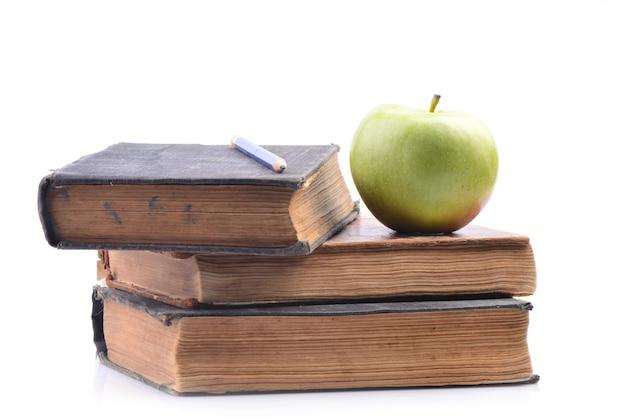 Książki i jabłko na białym tle