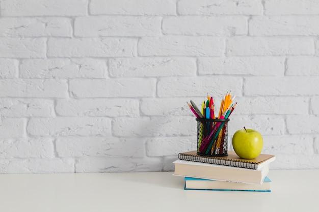 Książki, jabłko i kredki na stole