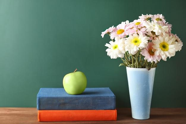 Książki, jabłko i kwiaty na drewnianym stole