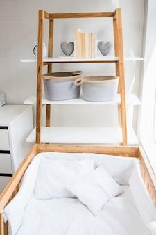 Książki, kształt serca i kosz umieszczony na półce w pobliżu podstawki w sypialni