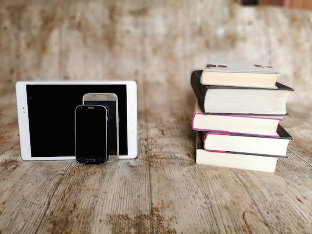 Książki lub urządzenia mobilne wybór między tabletami, telefonami komórkowymi a klasycznymi zasobami