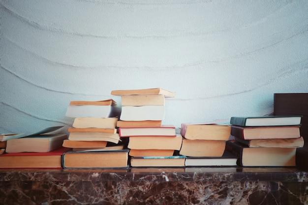 Książki na półce w bibliotece. zdjęcie w stylu vintage. koncepcja dnia edukacji i książki.