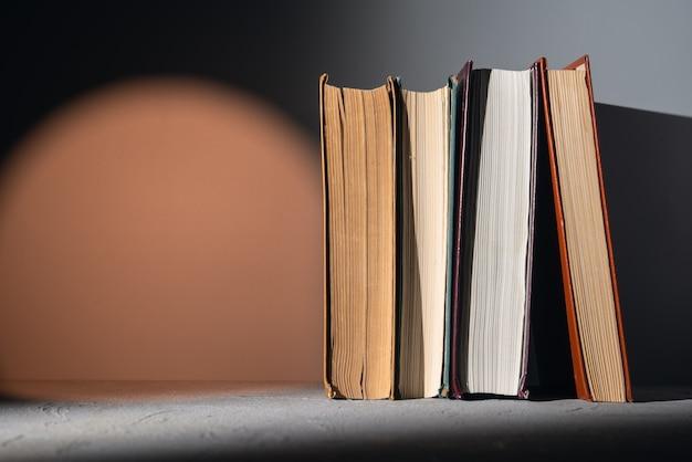 Książki na półce z jasną pomarańczową plamą światła