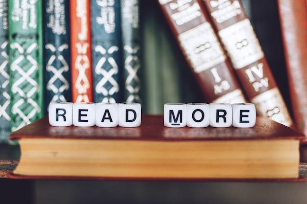 Książki na półce ze słowami czytaj więcej