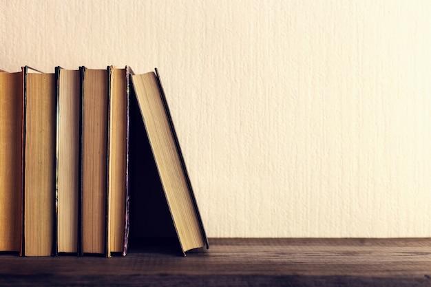 Książki na starej drewnianej półce.