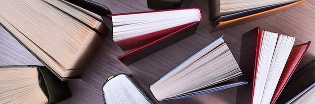 Książki na stole, widok z góry. w książkach arkusze są rozłożone w formie wachlarza, cienie książek na jasnym drewnianym stole. powrót do szkoły. szkolenie, edukacja, czytanie, nauka.