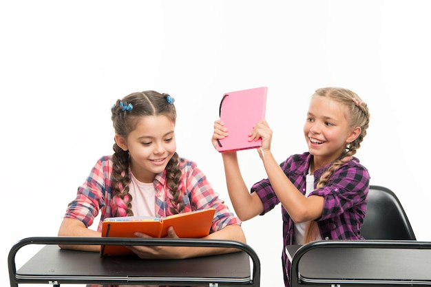 Książki nie służą do bicia. niegrzeczna dziewczynka psuje koleżankę z klasy za walkę o książki na białym tle. zabawne dziecko bawiąc się podczas gdy mały uczeń czyta książkę. książki edukacyjne dla uczniów.