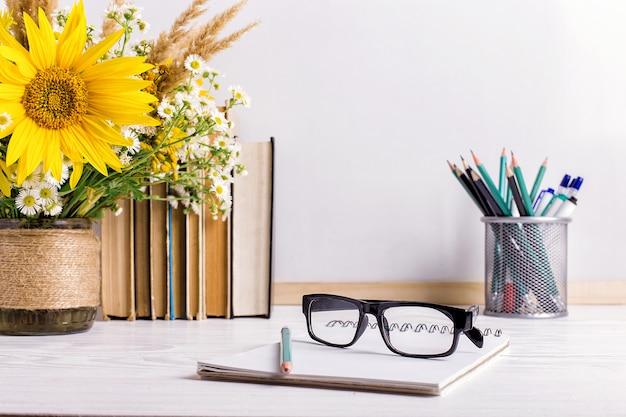 Książki, okulary, markery i bukiet kwiatów w wazonie na białym tle