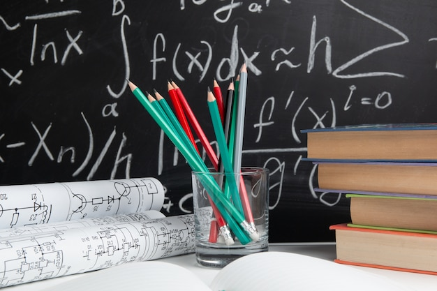 Książki, rysunki i ołówki na tle tablicy. koncepcja edukacji.