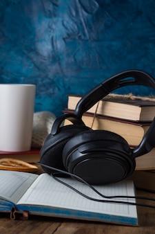 Książki są ułożone w stos, słuchawki, biały kubek, otwarty dziennik na drewnianym. koncepcja książek audio