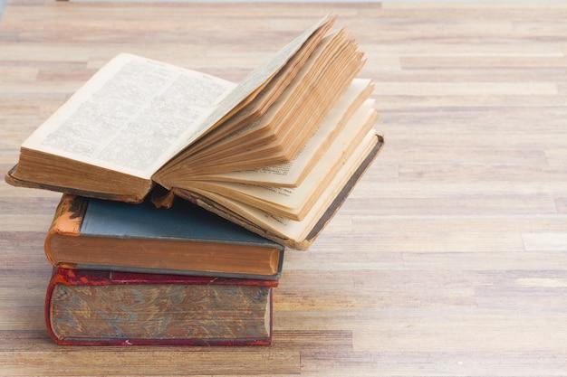 Książki stos z otworzyć jeden na tle drewniany stół