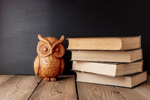 Książki ułożone na drewnianym stole w stylu rustykalnym z tablicą szkolną.