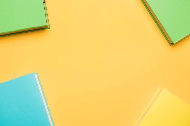 Książki w kolorowych pokrywach na żółtym tle