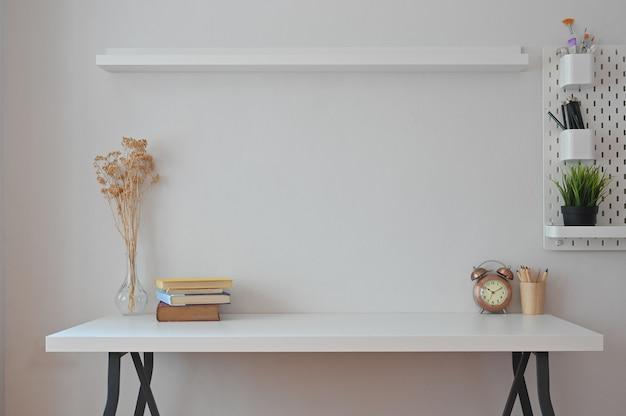 Książki z miejscem do pracy, suchy kwiat, zegar, ołówek i doniczka z półkami i tablicą na kołki.