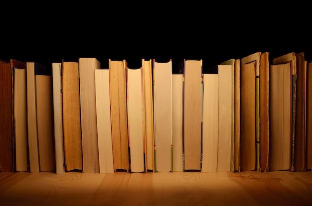 Książki z rzędu na drewnianej półce z ciemnym tłem