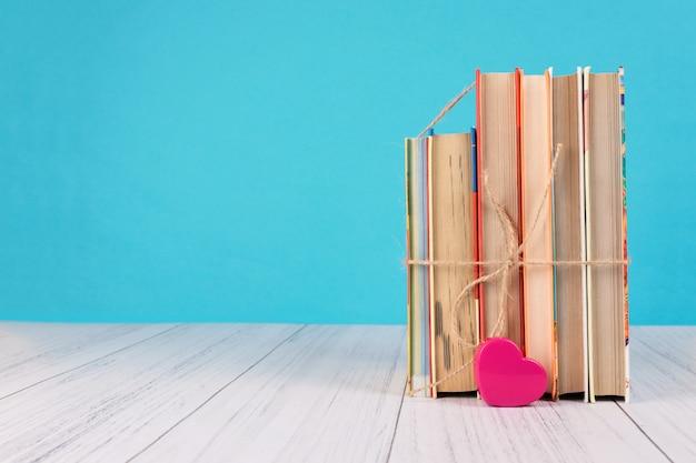 Książki z tasiemkowym łękiem jako prezent na błękitnym tle