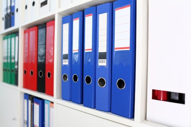 Książkowa półka pełno kartoteki falcówka w biurowym zbliżeniu