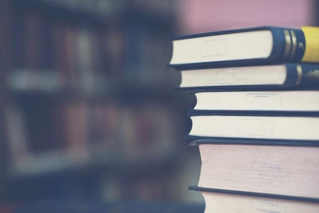 Książkowa sterta na drewnianym biurku i zamazanym półka na książki w bibliotecznym pokoju, edukaci tło