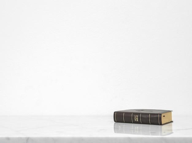 Księga biblijna postawiona na blacie stołu białego marmuru