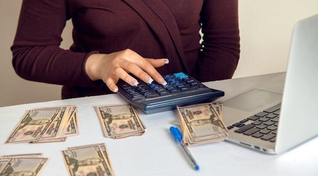 Księgowa bierze pod uwagę pieniądze w walucie dolara na kalkulatorze