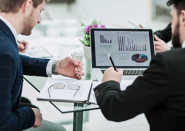 Księgowa firmy omawia wykresy finansowe rozwoju firmy na stanowisku pracy w biurze