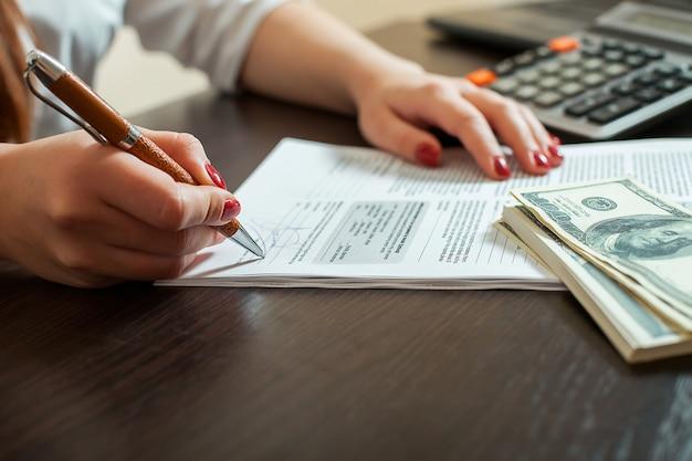 Księgowa kobieta podpisuje dokumenty księgowe