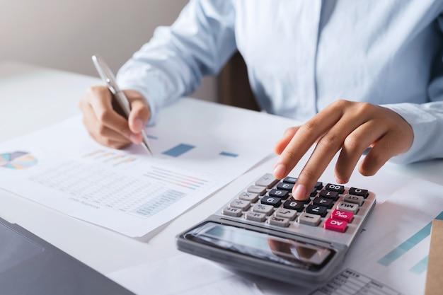 Księgowa kobieta używać kalkulatora i komputera z przytrzymaniem pióra na biurku w biurze