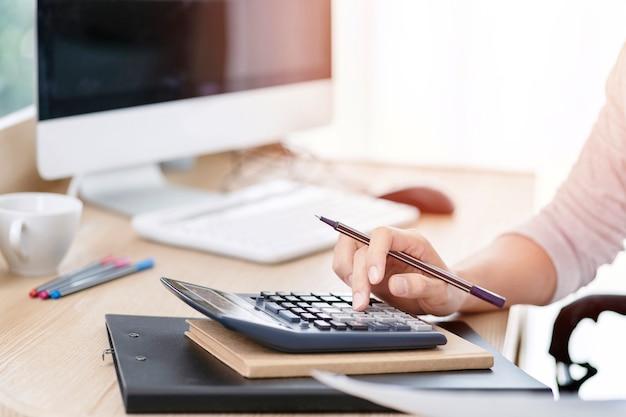 Księgowa kobieta za pomocą kalkulatora do liczenia dochodu pracującego na kontach w analizie biznesowej i dokumentowania raportu danych finansowych z komputera przenośnego w biurze, koncepcja biznesowa.