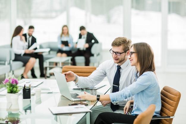 Księgowi pracują na laptopie z wykresami finansowymi firmy w nowoczesnym biurze.