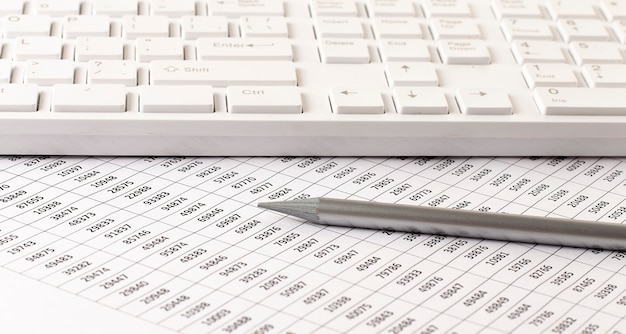 Księgowy biznesowy pracuje z podatkami i klawiaturą na białym widoku z góry biurka