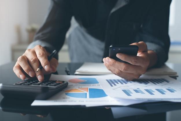 Księgowy człowiek za pomocą kalkulatora do obliczania danych biznesowych i raportu finansowego w biurze