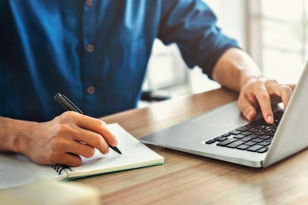 Księgowy firmy używać pióra i komputera na biurku w biurze. koncepcja finansów i rachunkowości