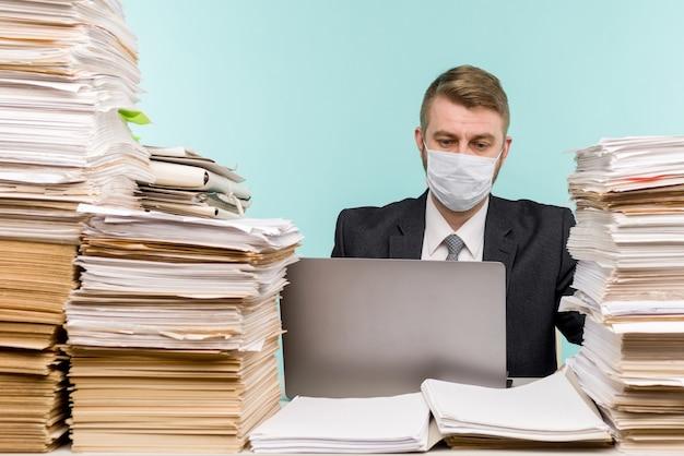 Księgowy lub kierownik firmy pracuje w biurze w pandemii ze względu na nagromadzoną papierkową robotę.