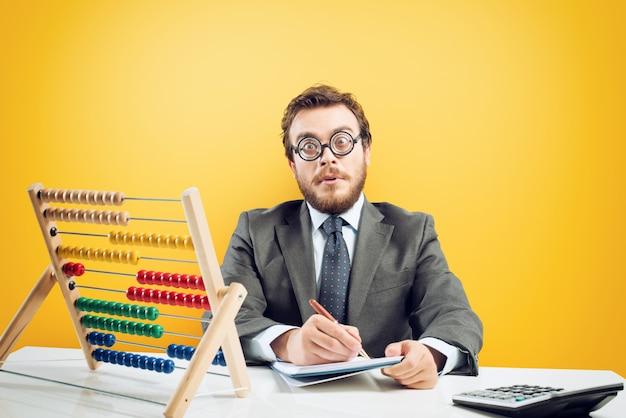 Księgowy nerd wykonuje skomplikowane obliczenia przychodów firmy na żółtym tle