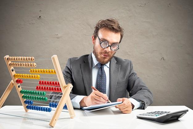 Księgowy nerd wykonuje złożone obliczenia przychodów firmy