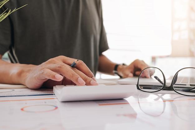 Księgowy pracuje na kalkulatorze kalkulować pieniężnego raport, dokument księgowego i komputer przy biurem, biznesowy pieniężny pojęcie