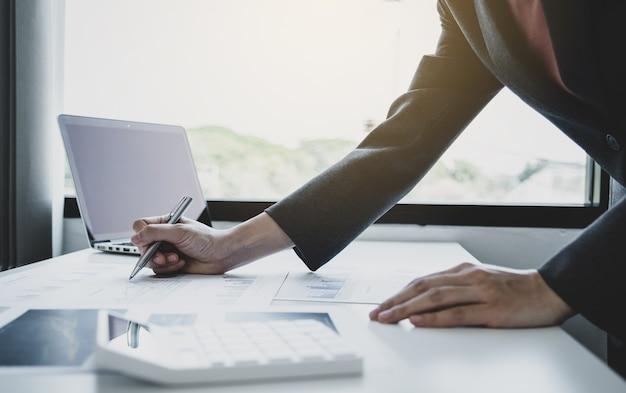 Księgowy przedsiębiorców ręka trzyma pióro i robi konto do płacenia podatku na białym biurku w biurze pracy.