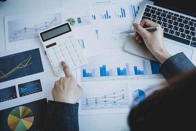 Księgowy przedsiębiorców ręka trzyma pióro za pomocą kalkulatora i laptopa robi konto