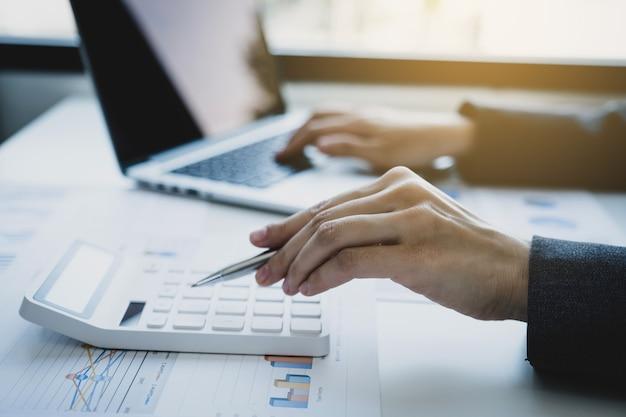 Księgowy przedsiębiorców używa kalkulatora i laptopa do rozliczania podatku w biurze pracy