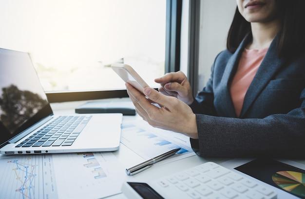 Księgowy przedsiębiorców używa smartfona i laptopa do rozliczenia podatku w biurze pracy