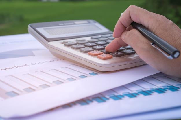 Księgowy ręce obliczają wykres raportu finansowego, licząc na kalkulatorze